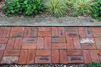 Red brick path edged with oak sleeper and mixed border.