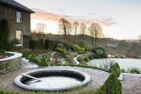 A circular pond set into a formal terrace is surrounded by lowhedging and planting in a country garden
