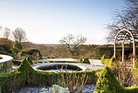 A circular pond set into a formal terrace is surrounded by low Buxus - Box -hedging and planting in a country garden
