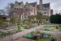 The Leisure Garden with a stone urn and variegated clipped box at its centre, Rodmarton Manor, Glos, UK.