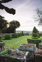 The Topiary Garden edged with stone troughs, a wall and urns, with countryside beyond at Rodmarton Manor, Glos, UK.