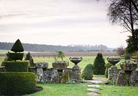 Pair of classic urns displayed on stone wall in the Topiary garden, with views out to surrounding fields at Rodmarton Manor, Glos, UK.