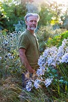 Nick Macer in the garden with Agapanthus 'Windsor Grey' in foreground, Pan Global Plants, Frampton on Severn, Gloucestershire, UK.