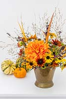 Autumnal arrangement including Rudbeckia, Helenium, Dahlia, Salvia and ornamental grasses in brass vase.