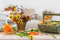 Partially-made autumnal arrangement on table with Rudbeckia, Helenium, Dahlia, Salvia and ornamental grasses.