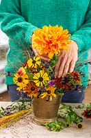 Woman adding a bright orange Dahlia to an autumnal arrangement in brass vase.