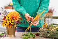 Woman using secateurs to trim ornamental grasses to size for arrangement.