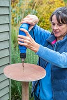 Woman using electic screwdriver to fix wooden disk to post