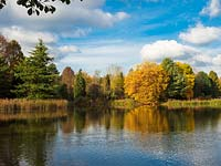 Looking across the lake at Bodenham Arboretum with lots of autumn colour and a blue sky.