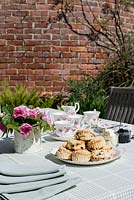 Outdoor table with laid out for a traditonal afternoon tea with roses in a jug