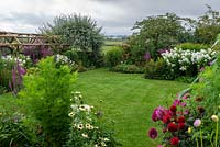 Looking out from a half-acre country garden over dahlias, lawns and borders of summer perennials, to a rural vista of Blackmore Vale with fields, spinneys and distant hills.