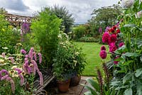Looking out from a half-acre country garden over dahlias, a rustic pergola, lawns and borders of summer perennials, to a rural vista of Blackmore Vale.