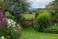 View to wooden gate at the end of the garden, with view to field and vales beyond.