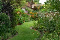 Views through a half-acre country garden, along a wide curving grass path, to borders of summer herbaceous perennials and pots of dahlias.