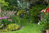Views through a half-acre country garden past borders of summer herbaceous perennials and pots of dahlias, along a wide curving grass path to a bench in the shade of a tree.