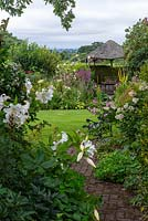 Views along a brick path to a wooden gazebo, flanked by borders of summer herbaceous perennials. Beyond, glimpses of Blackmore Vale.