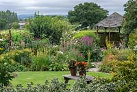 A wooden gazebo is flanked by borders of summer herbaceous perennials including mallows, lythrum, linaria, verbascum and phlox, with glimpses of Blackmore Vale beyond.