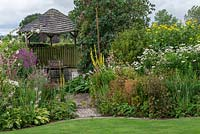 A wooden gazebo is flanked by borders of summer herbaceous perennials including mallows, lythrum, linaria, verbascum, rudbeckias, shasta daisies, liatris and phlox.