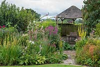 A wooden gazebo is flanked by borders of summer herbaceous perennials including mallows, lythrum, linaria, verbascum, shasta daisies, liatris and phlox.