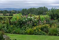 Border planted with dahlias and herbaceous perennials including linaria, helianthus, verbascum and phlox. Beyond, glimpses of Blackmore Vale.