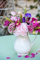 Peony in white jug with sweet williams, sweet peas and grass seedheads