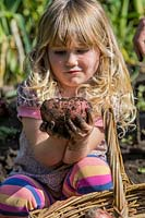 Little girl holding a Potato covered in mud