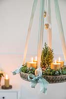 Hanging advent arrangement with gold candles, miniature christmas tree, Eucalyptus and Hebe foliage