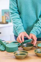 Woman adding oasis to holders to keep the foliage fresh