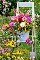 Bucket of cut summer flowers standing on stepladder.