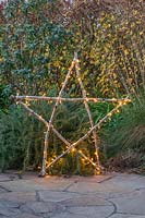 Illuminated natural star with fairylights made from lengths of Hazel sticks in front of shrub border