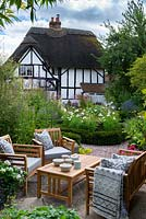View over seating area to yew-edged beds of tall perennials, ornamental grasses and Cosmos, thatched cottage beyond