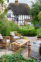 View over a seating area to yew-edged beds of tall perennials, ornamental grasses and Cosmos, thatched cottage beyond