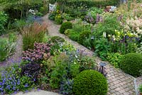 A bird's eye view of a contemporary garden design, a diagonal brick path separates a gravel garden from beds of perennials and grasses, interspersed with Taxus - Yew ball topiary