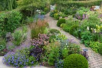 A bird's eye view of a contemporary garden design, a diagonal brick path separates a gravel garden from beds of perennials and grasses, interspersed with Taxus - Yew - ball topiary