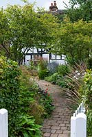 A brick path from gate to cottage, beds either side with multi-stemmed Amelanchier lamarchii underplanted with perennials