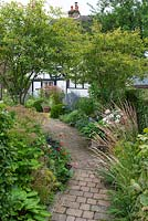 A brick path cuts diagonally through the garden, passing by two multi-stemmed Amelanchier lamarckii, to cottage