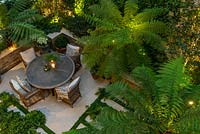 A bird's-eye view of an enclosed courtyard with outdoor dining, the fronds of Dicksonia antarctica - Tree Fern - filtering the light from uplighters