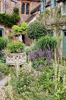 Courtyard gravel garden with large ornate natural stone urn and planting which includes Verbascums, Nigella damascena -love-in-a-mist, and Salvias.