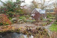 View over pond to garden seating with greenhouse beyond