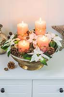 An arrangement in a golden bowl, with four coral pillar candles, Poinsettia flowers and cones