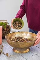 Woman adding gravel to gold bowl to raise the level and add stability