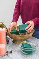 Woman placing blocks of floral foam, soaked in water, on top of the gravel in gold bowl