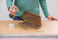 Woman spraying basket green using a spray can