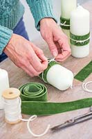 Woman adding a decorative velter green ribbon and cream string to the pillar candle