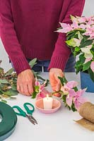 Woman sealing end of flower stem by holding it in flame for 30 seconds
