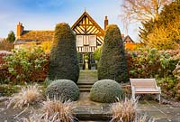 View of the house from the Lower Rill Garden on a frosty December morning. Planting includes: Iris ensata, clipped yew trees, balls and hedge 'Taxus baccata' a beech hedge 'Fagus' and Hydrangea macrophylla.