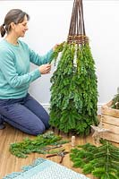 Woman using brown garden twine to attach pieces of conifer - juniperus foliage to willow obelisk frame