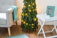 Space saving Christmas Tree made with pine - Abies and conifer - Juniperus foliage attached to a willow obelisk and decorated with star decorations and lights in a modern living room setting with chair and sidetable