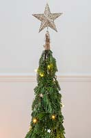 A decorative star on top of a space saving Christmas tree decorated with stars and lights