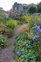 View over path and perennial flower borders towards house
